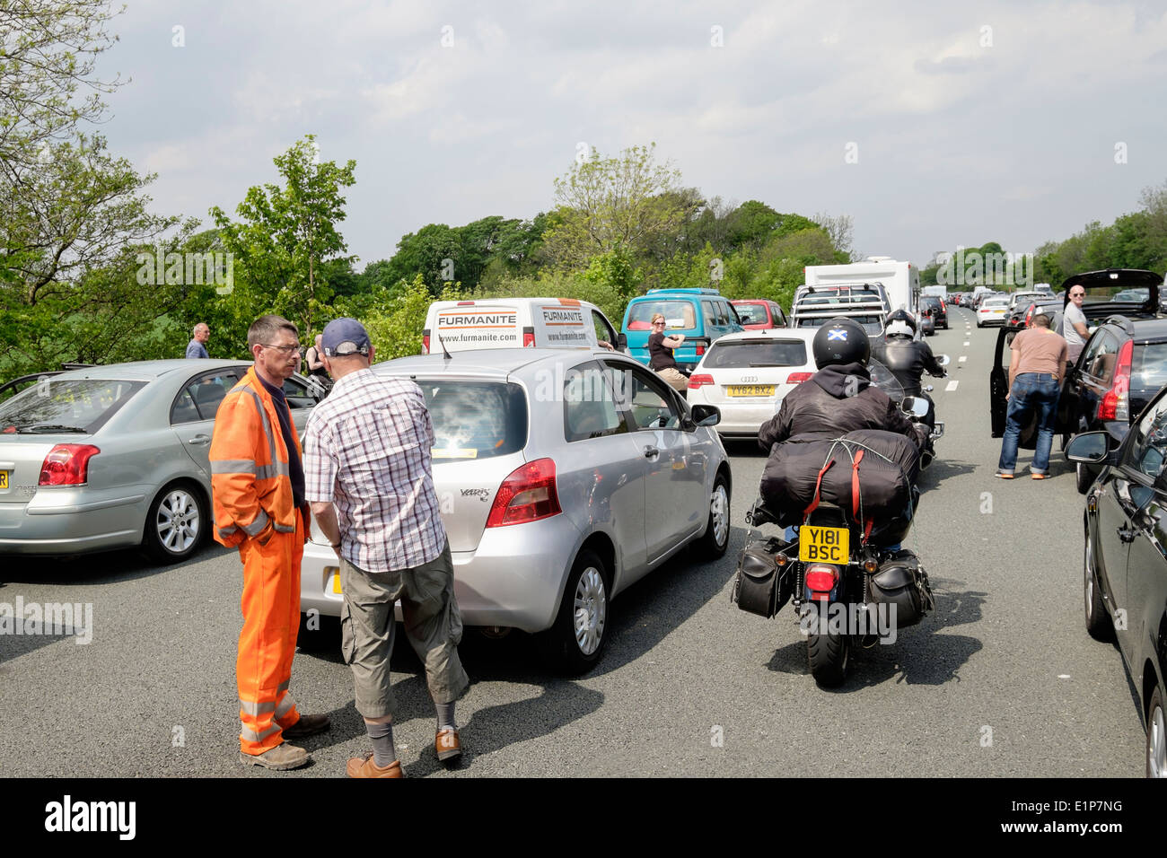 People standing on carriageway outside stationary vehicles in a traffic jam on M6 motorway due to accident causing long delay. Lancashire England UK - Stock Image