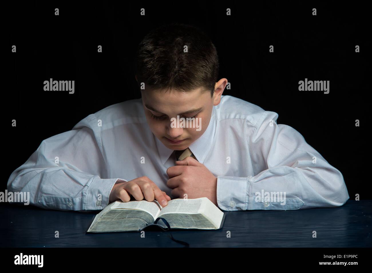 A teenage boy studies the scriptures. - Stock Image