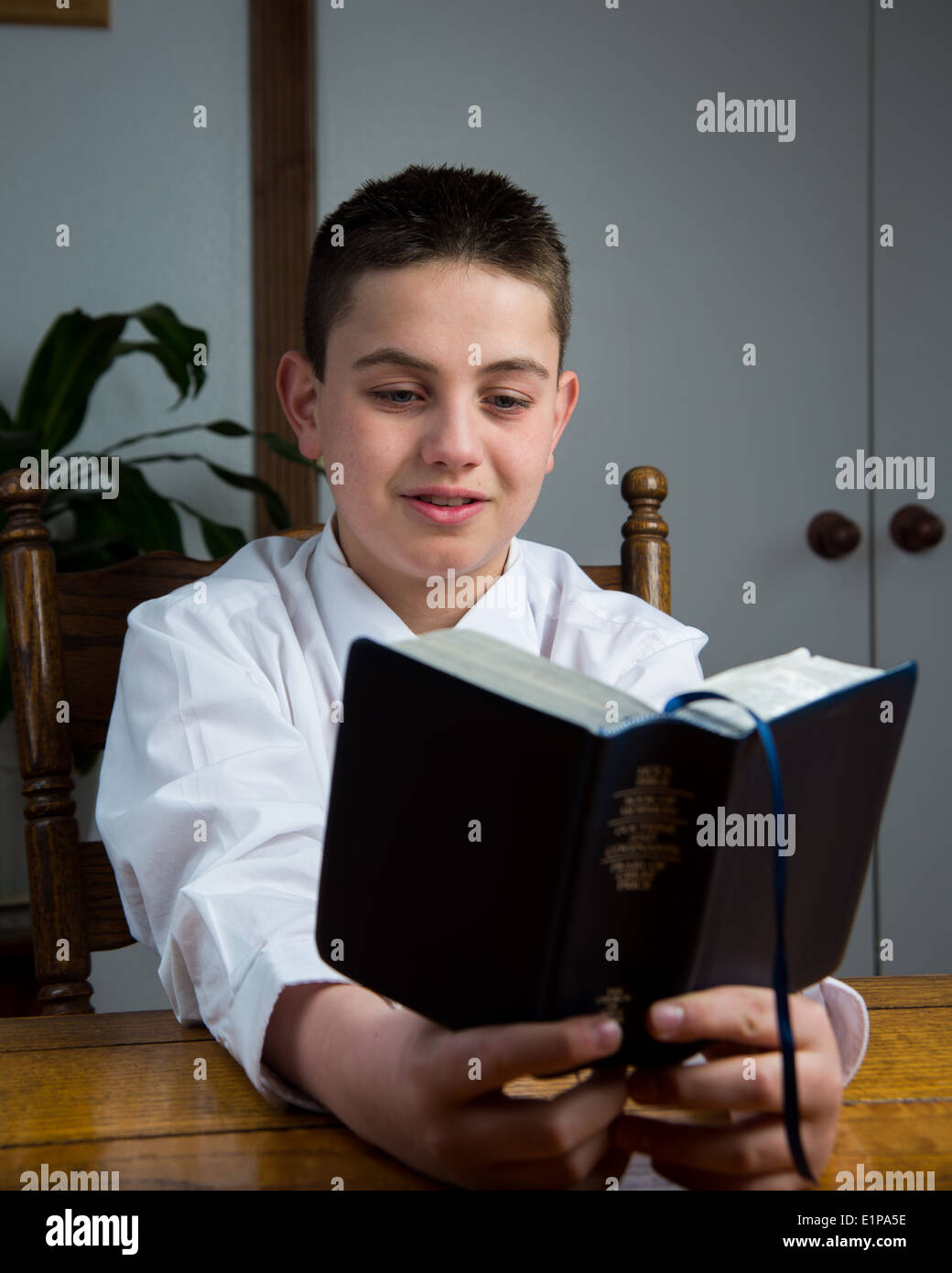 A young boy studying the scriptures. - Stock Image