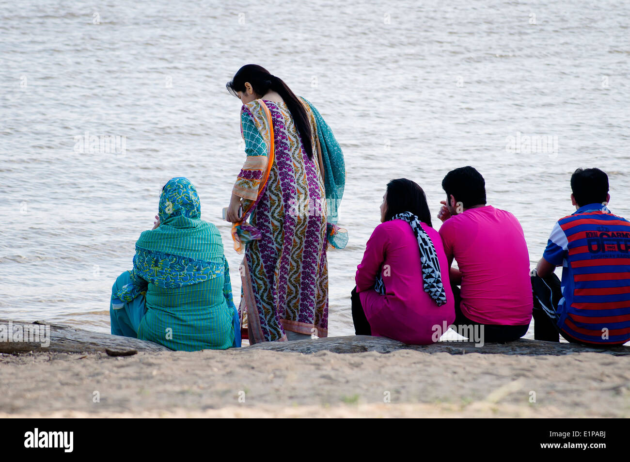 Young Asian Americans sitting on the bank of the Delaware River in the park, Philadelphia, USA - Stock Image