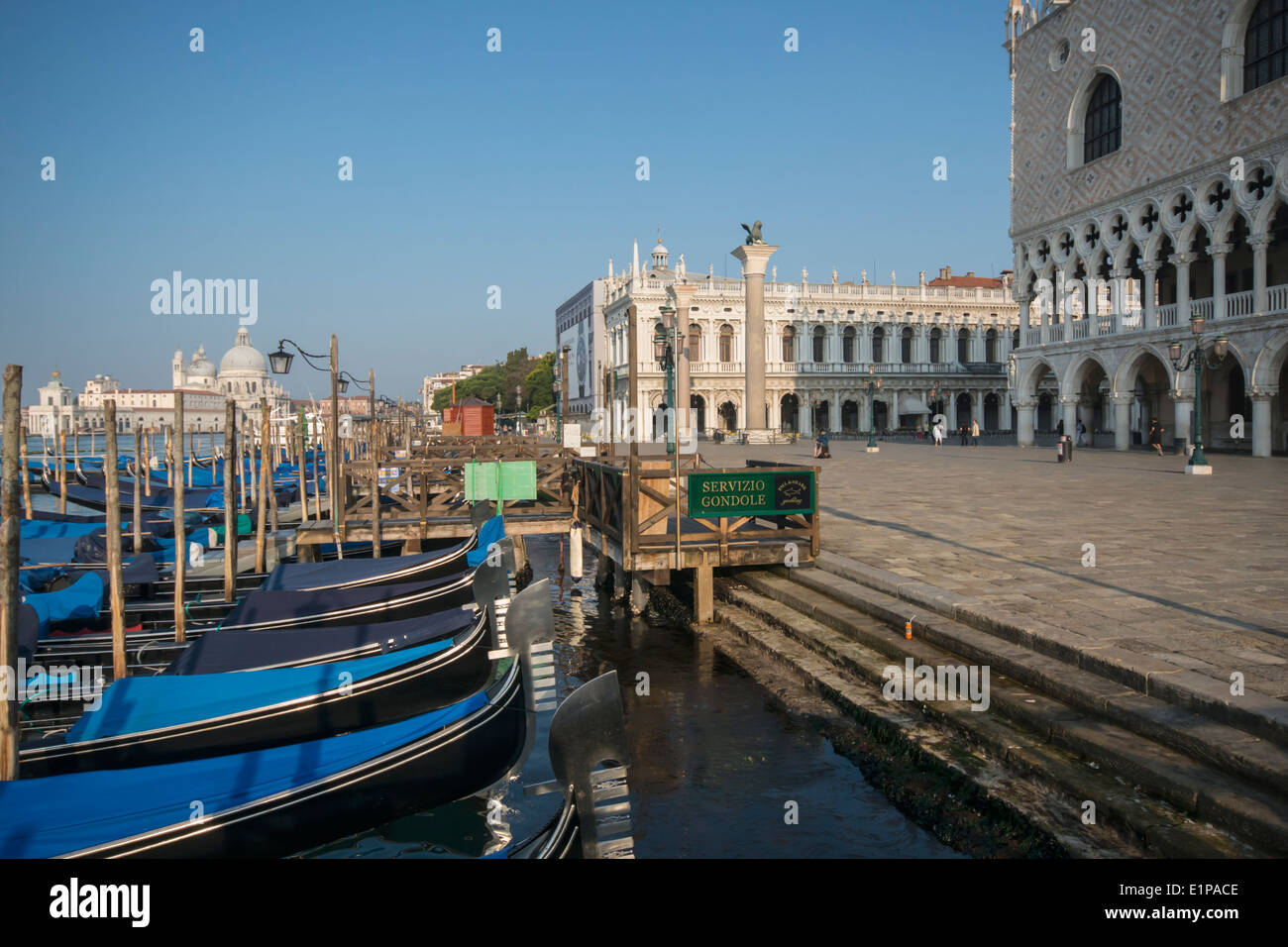 The Riva degli Schiavoni waterfront promenade in Venice, Italy, with gondolas to the left and the Doge's Palace Stock Photo