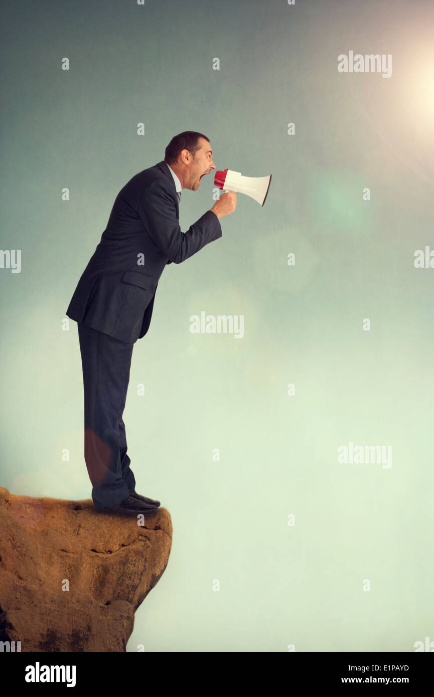 businessman with loudhailer on the edge of a cliff shouting - Stock Image