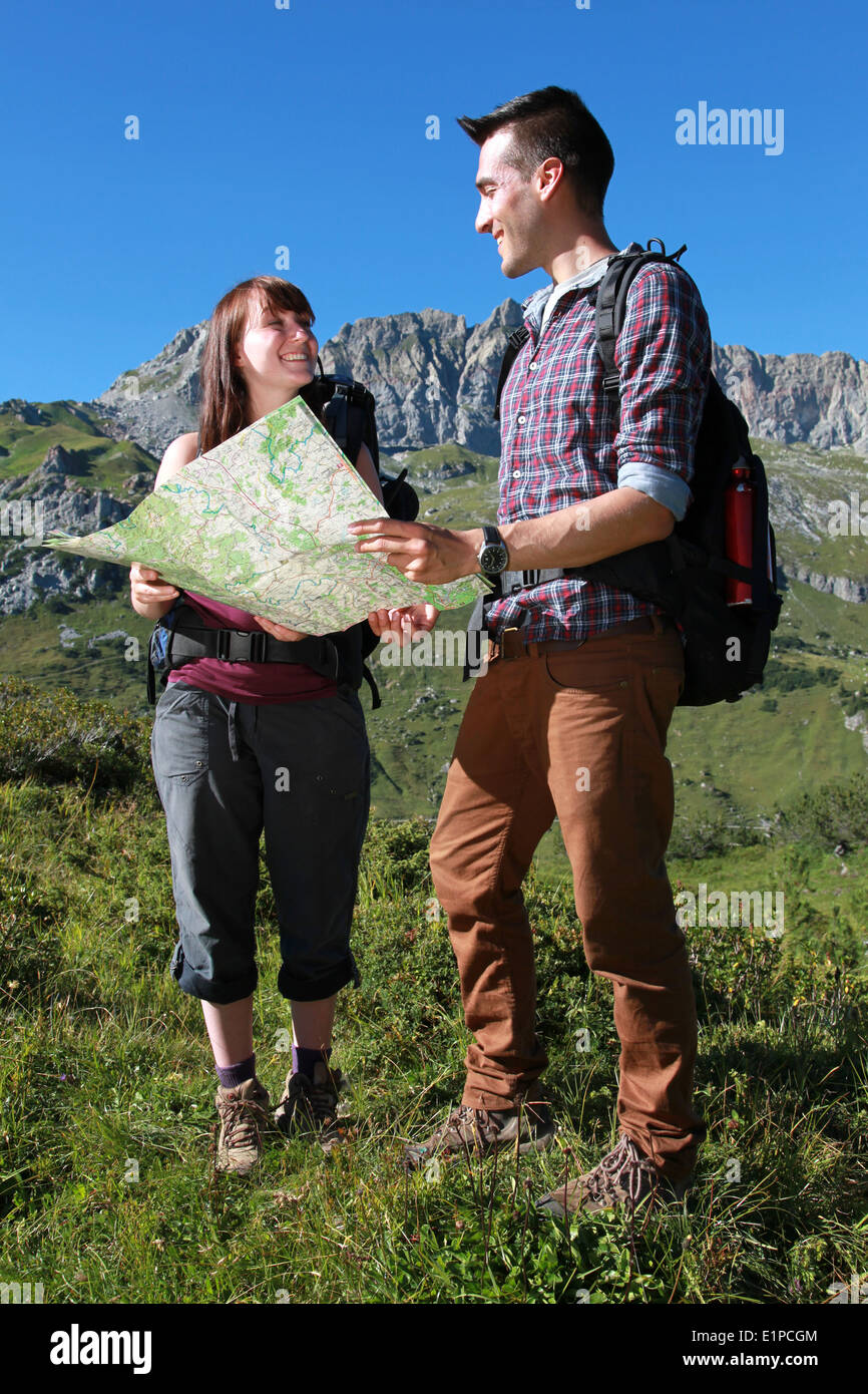 Young hikers reading a map for orientation in the mountains. - Stock Image