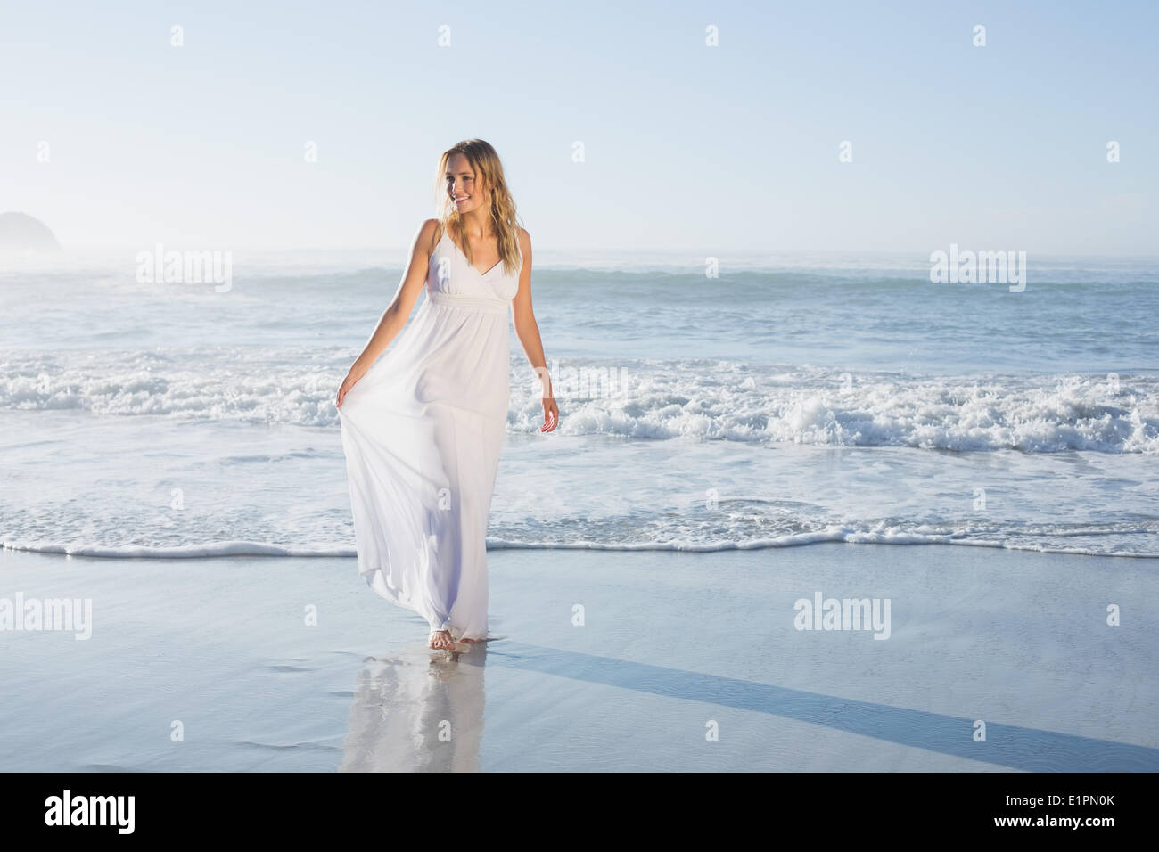 Pretty blonde at the beach in white sundress - Stock Image