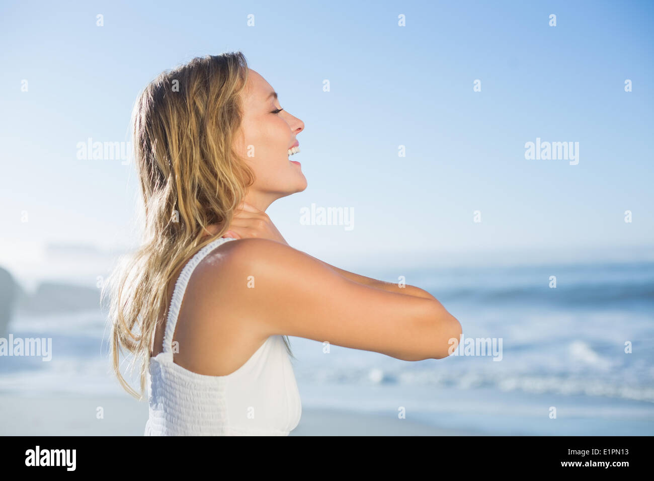 Pretty blonde standing at the beach in white sundress - Stock Image