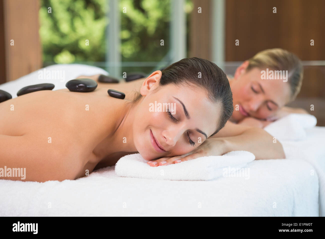 Pretty friends getting hot stone massages together - Stock Image