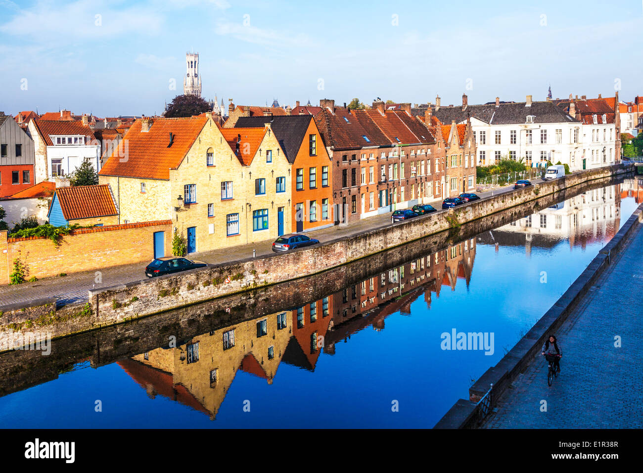 Medieval houses reflected in the canal along the Predikherenrei in Bruges, Belgium, with the Belfry tower in the distance. - Stock Image
