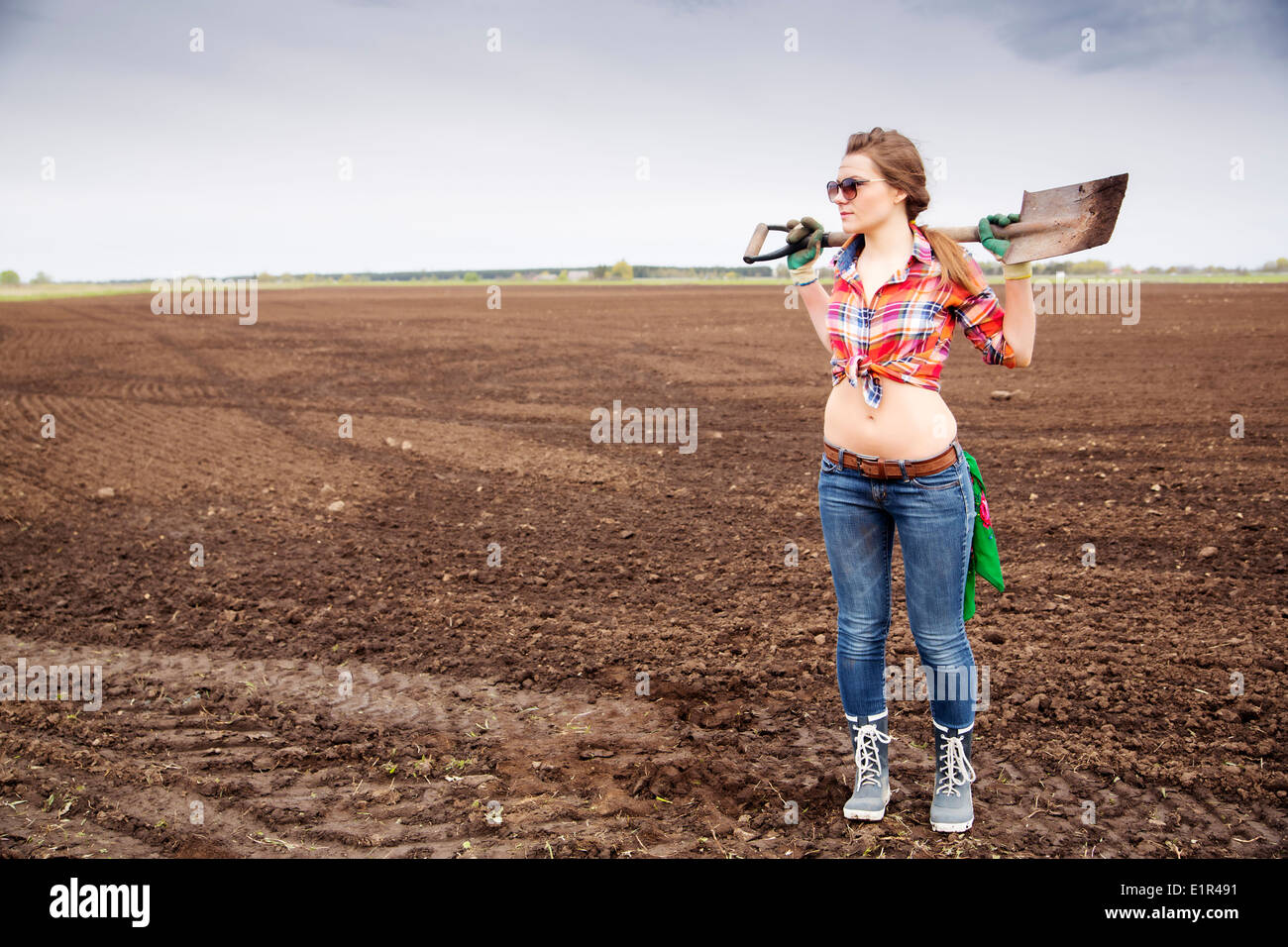 Young woman holding sharp shovel on weak shoulders - Stock Image