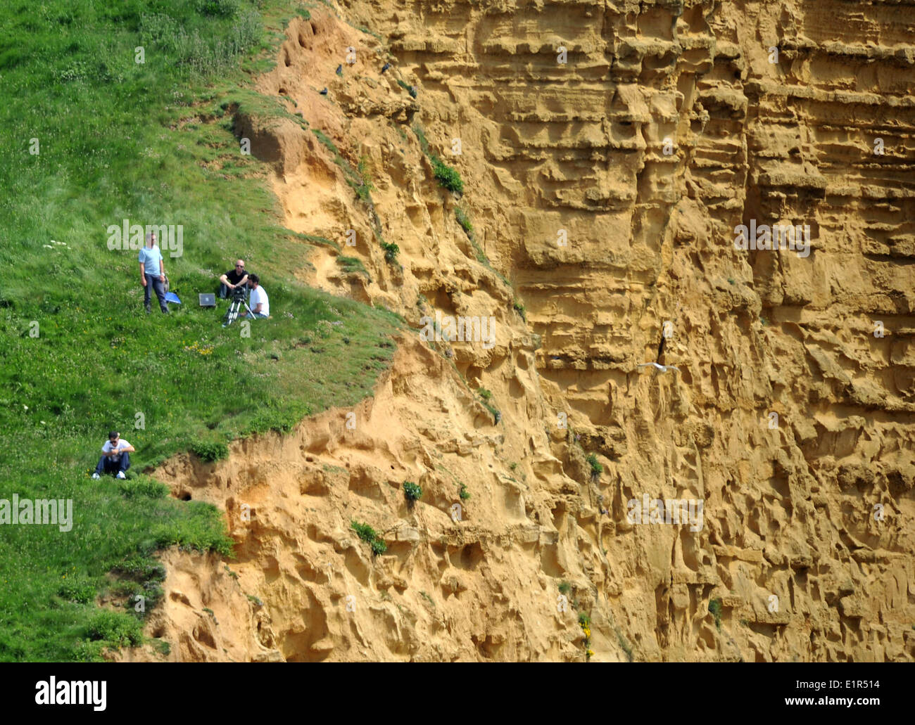 West Bay, Dorset, Britain, UK . 08th June, 2014. What can only be described as a crime too is this film crew working on the ITV crime series Broadchurch at West Bay in Dorset filming from a highly dangerous section of the icon cliffs used in the programme. Only a few months ago massive cliff falls have have occurred and this risky practice by the team has been criticised as foolhardy and dangerous. Credit:  Dorset Media Service/Alamy Live News - Stock Image