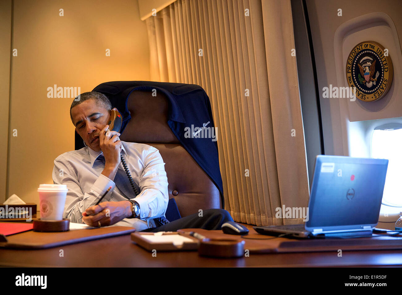 US President Barack Obama talks on the phone in his office aboard Air Force One April 10, 2014 on a flight back to Washington, DC. - Stock Image