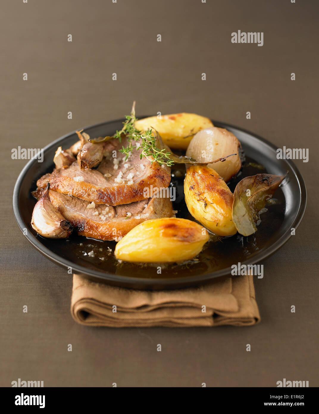 Leg of lamb with garlic,thyme and sauteed potatoes - Stock Image