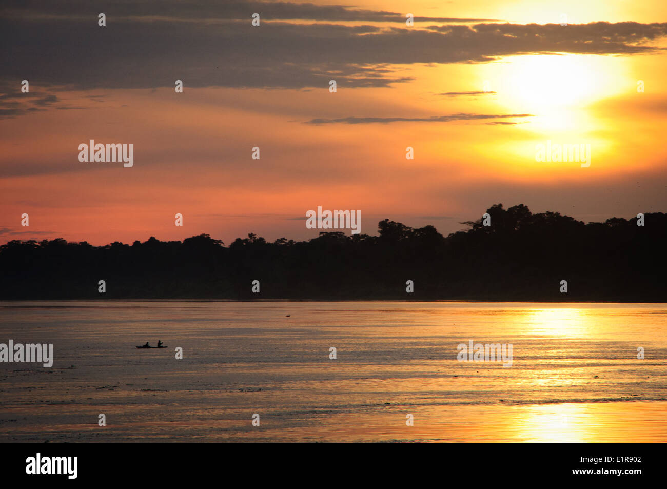 Little Boat on the Immense Peruvian Amazon River at Sunset - Stock Image