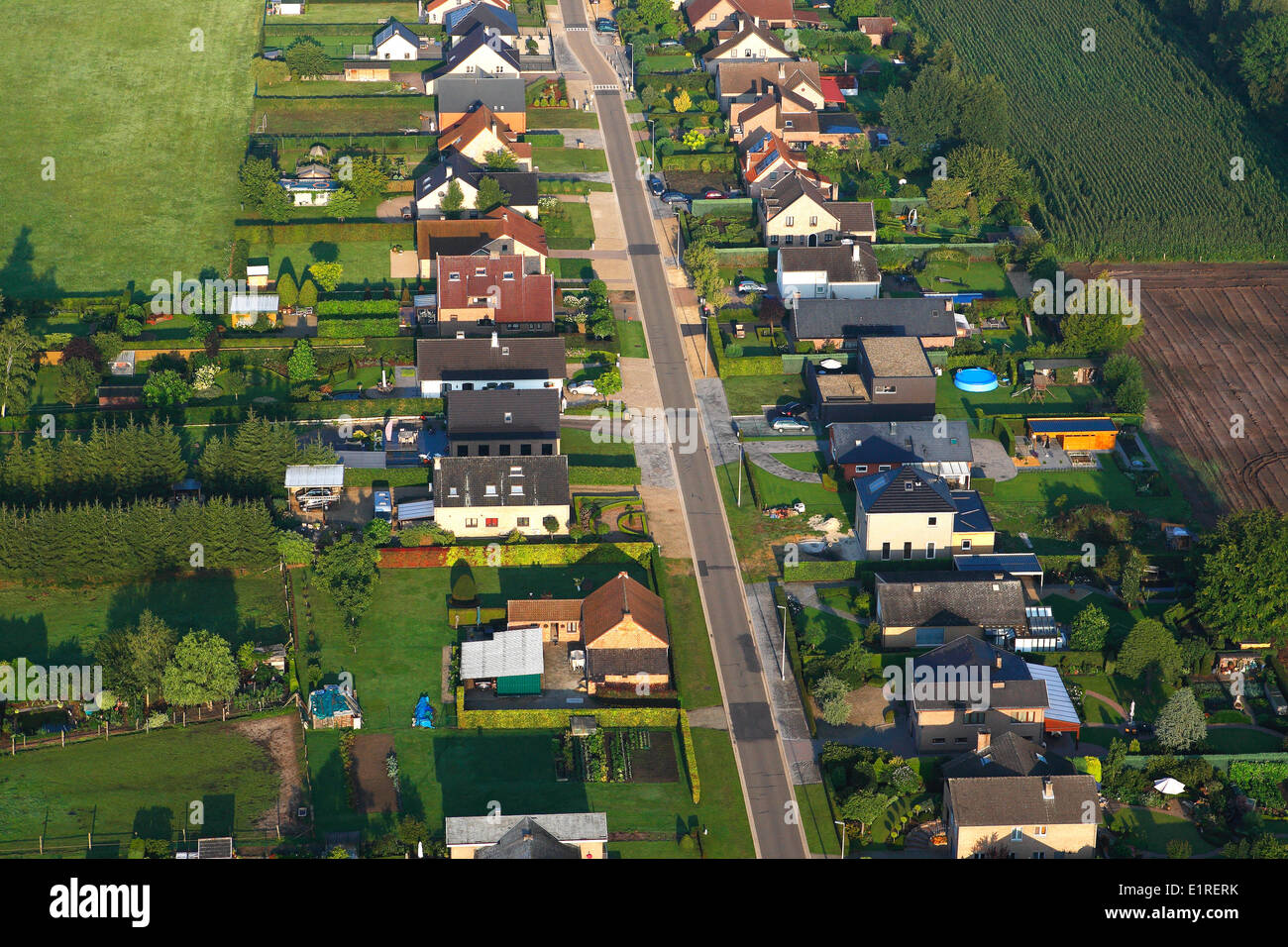 Urbanisation at the border of agricultural area with fields, grasslands and hedges, seen from the air, Belgium - Stock Image