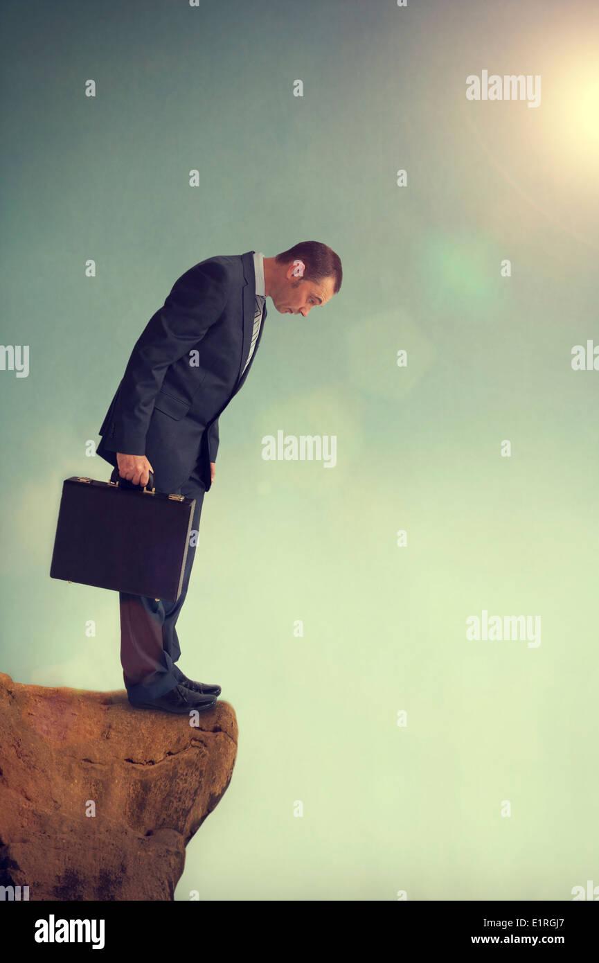 businessman in a predicament facing a dilemma on a cliff edge precipice - Stock Image