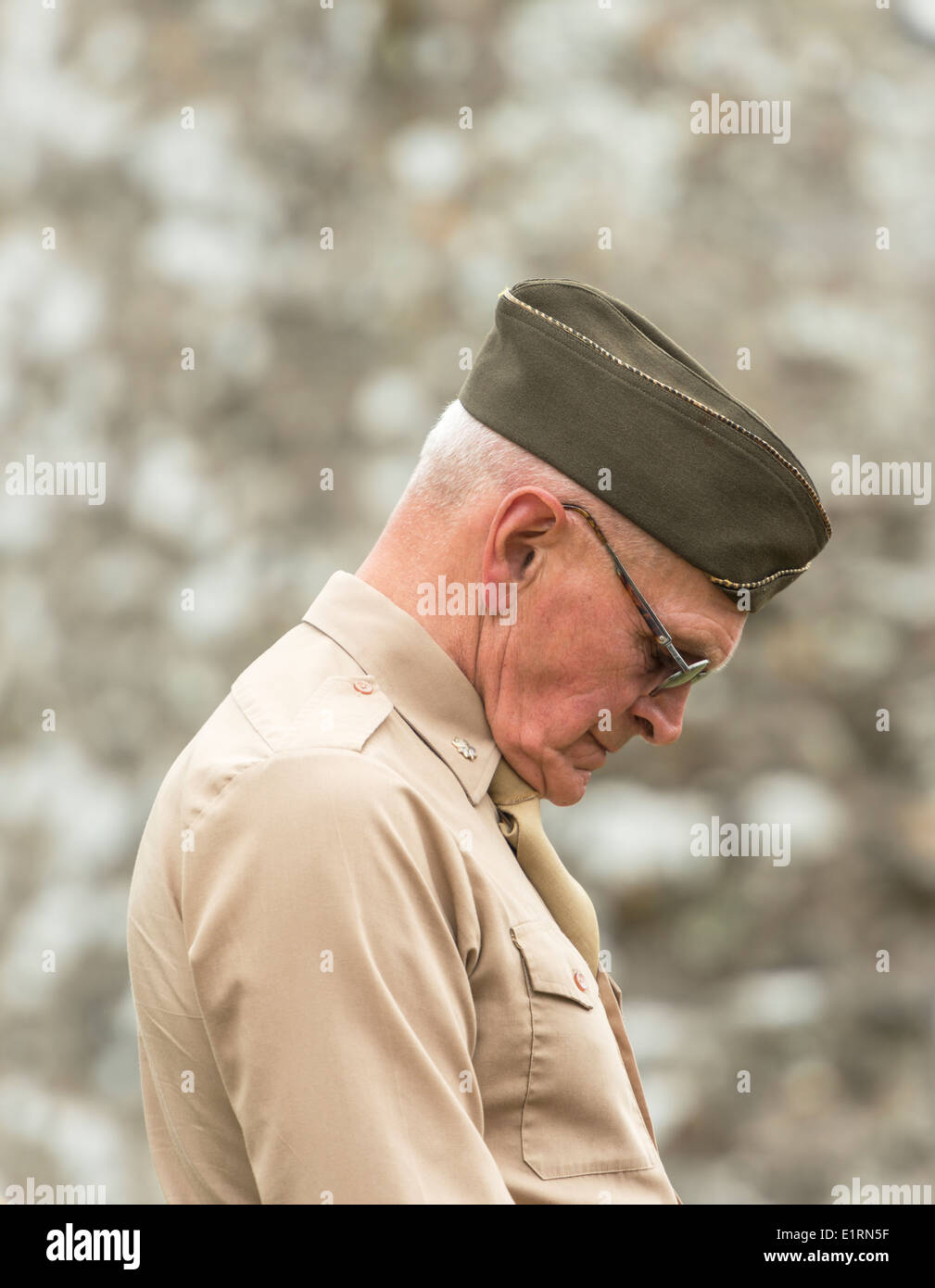 Man dressed as a World War 2 American serviceman bows his head in prayer - Stock Image