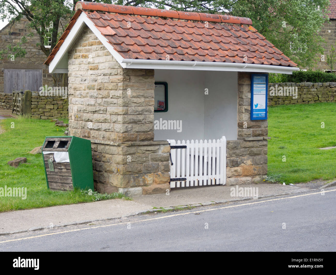 Substantial stone built village bus shelter with local notices inside and a gate to prevent sheep from entering - Stock Image