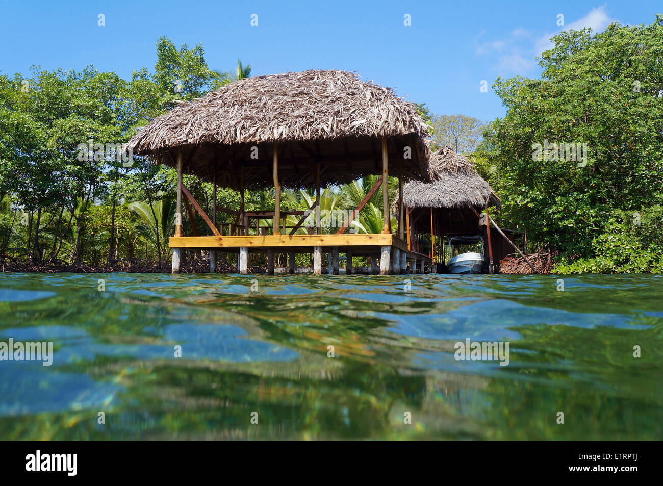 Tropical hut with thatch roof overwater and a boathouse with vegetation in background, viewed from water surface, Caribbean sea - Stock Image