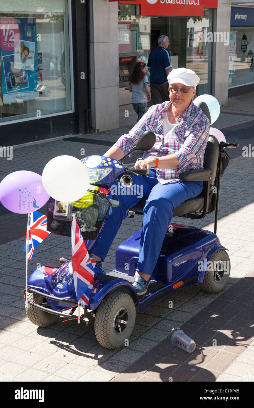 Person on decorated mobility scooter taking part in a charity 'fun run'. - Stock Image