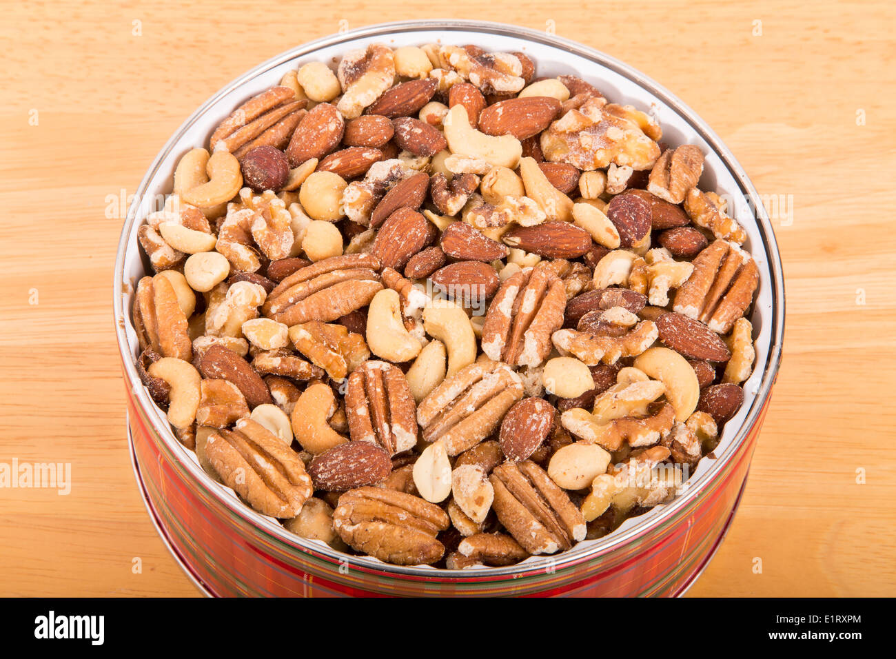 Deluxe mixed nuts in a round tin on a wood table - Stock Image