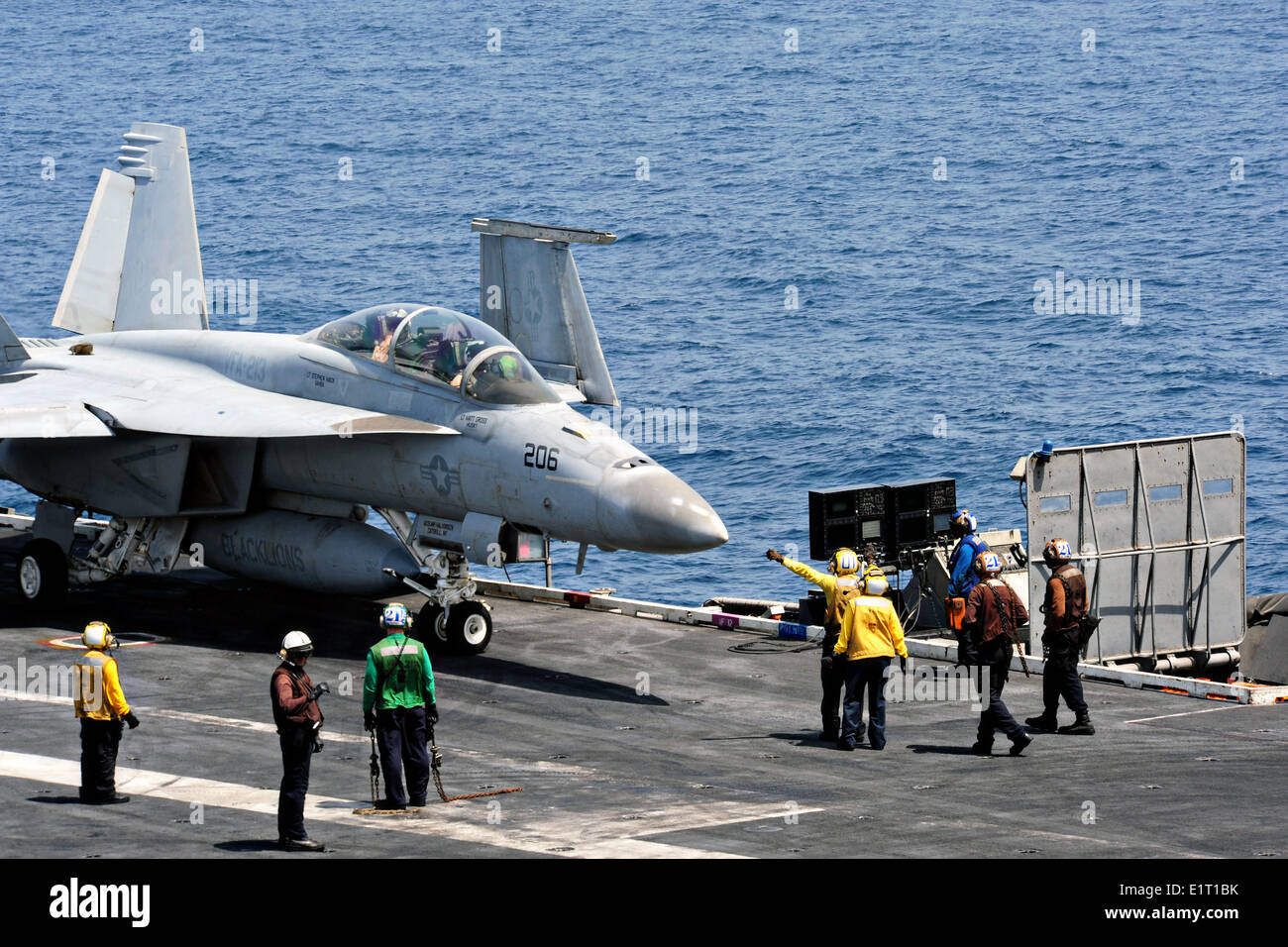 A US Navy sailors direct a F/A-18F Super Hornet fighter aircraft into launch position on the flight deck of aircraft carrier USS George H.W. Bush June 7, 2014 in the Arabian Sea. - Stock Image