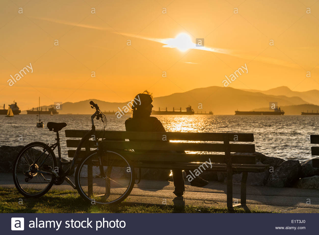 Woman on park bench at sunset, Vanier Park, Vancouver, British Columbia, CanadaVancouver, British Columbia, Canada - Stock Image