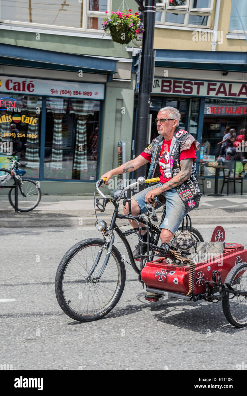 Man on bicycle (Multi-media artist Mad Dog) with punk sidecar with machine gun and helmeted dog, - Stock Image