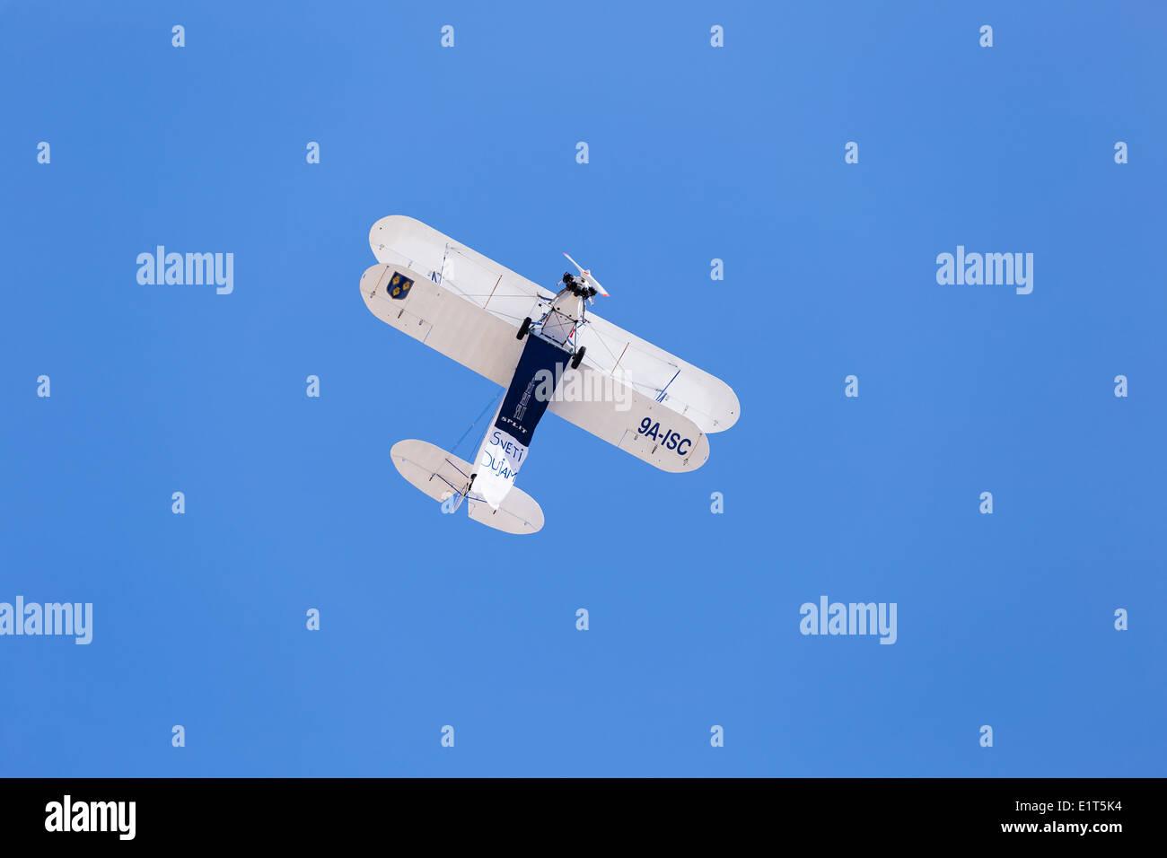 A bi-plane aircraft flies over riva trailing a banner for Sveti Dujam during the sudamja celebrations in split croatia - Stock Image
