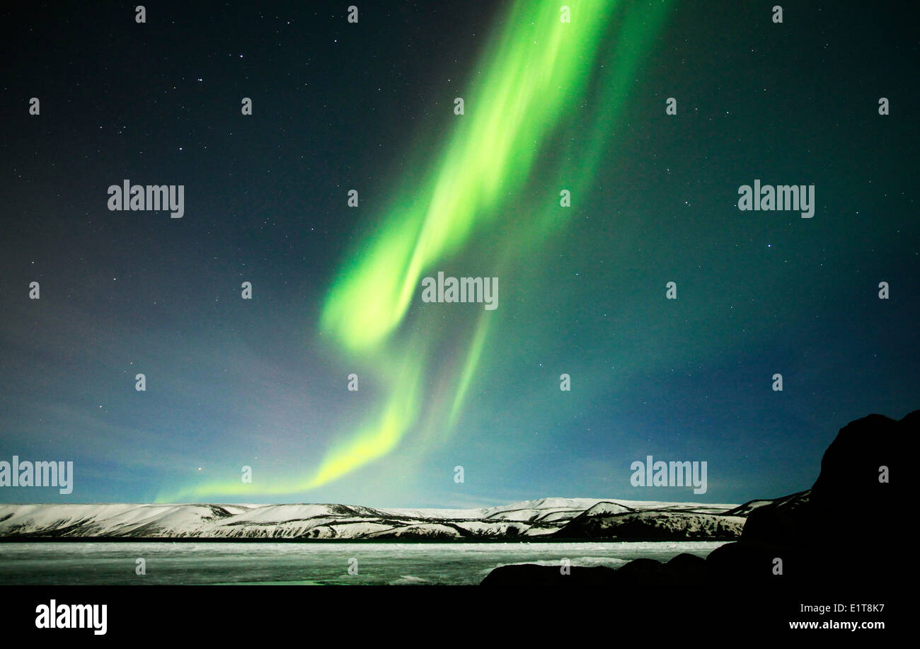 The Northern Lights shine above a frozen lake outside Reykjavik in Iceland Stock Photo