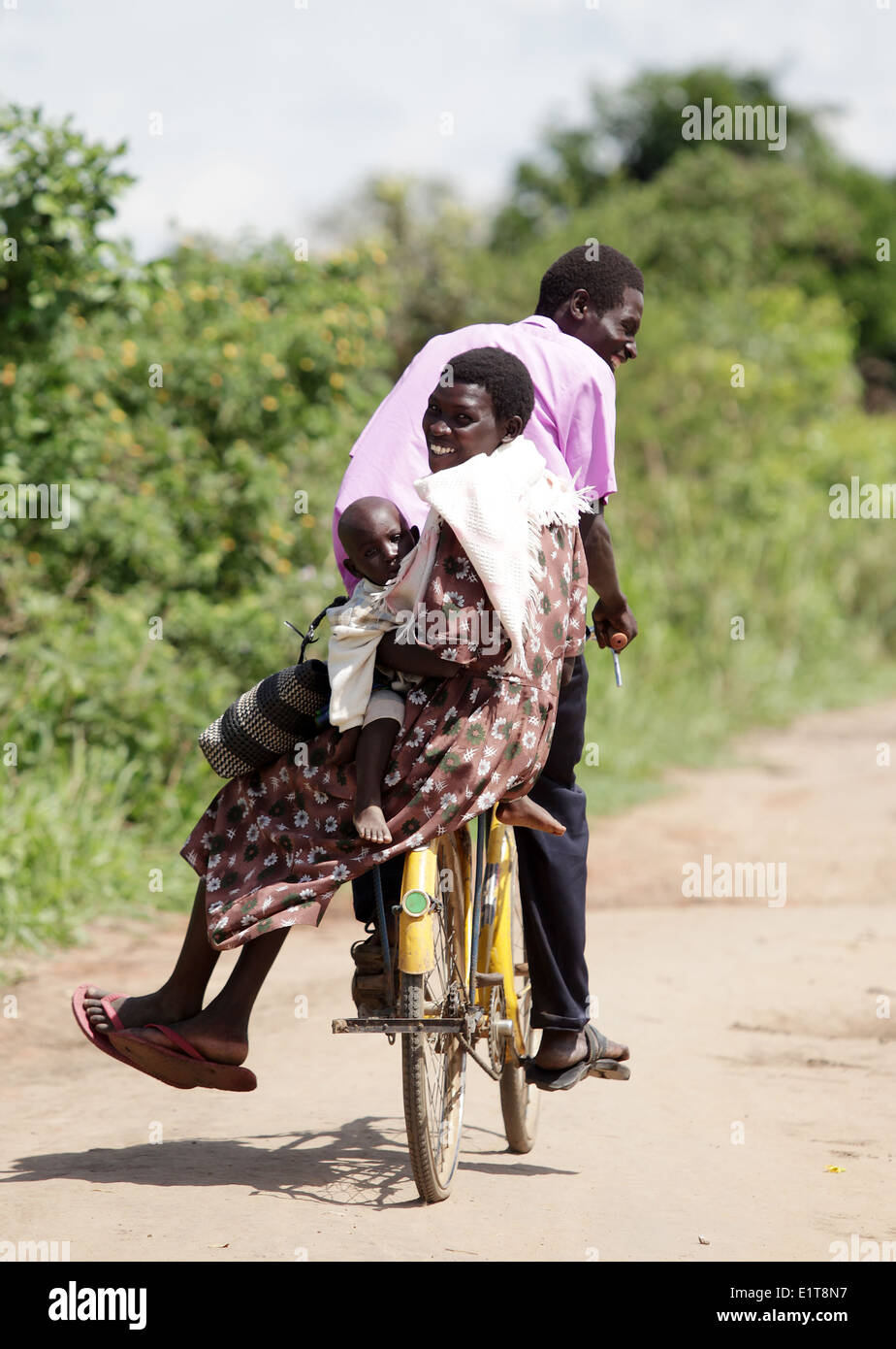 A family cycle in a rural part of the Lira district of northern Uganda. Stock Photo