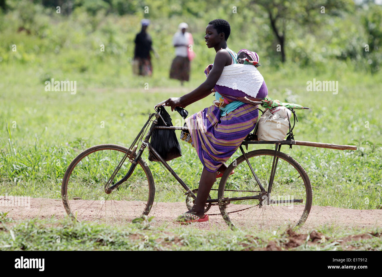 A mother and her baby cycle in a rural part of the Lira district of northern Uganda. Stock Photo