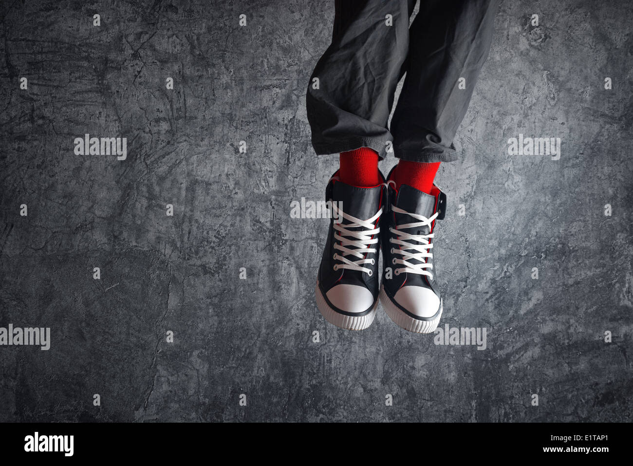 Excited man in sneakers jumping high in the air. Concept of freedom and youth spirit. - Stock Image