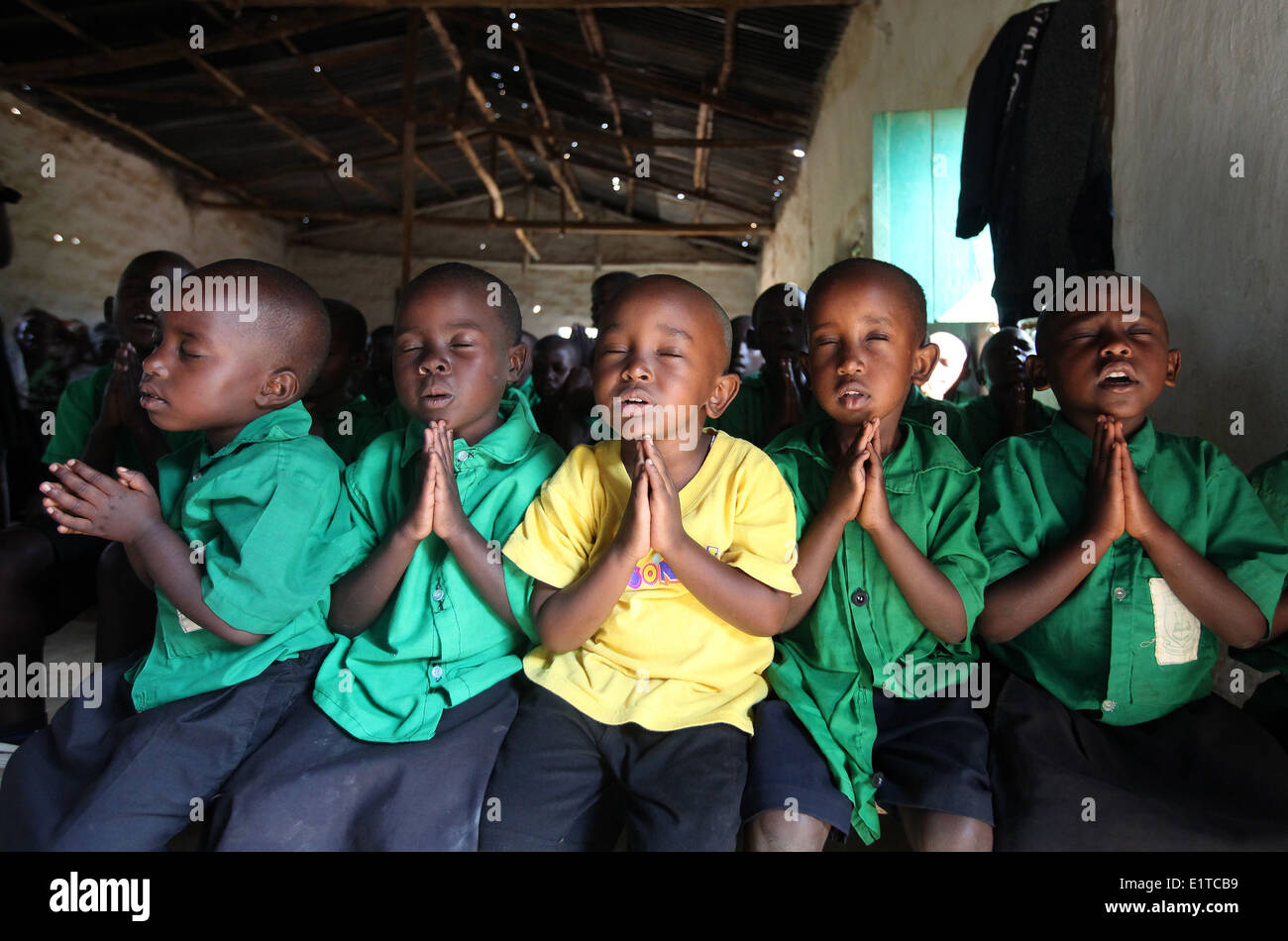 Children pray at a NGO funded school in the Nyagatare district of Rwanda - Stock Image