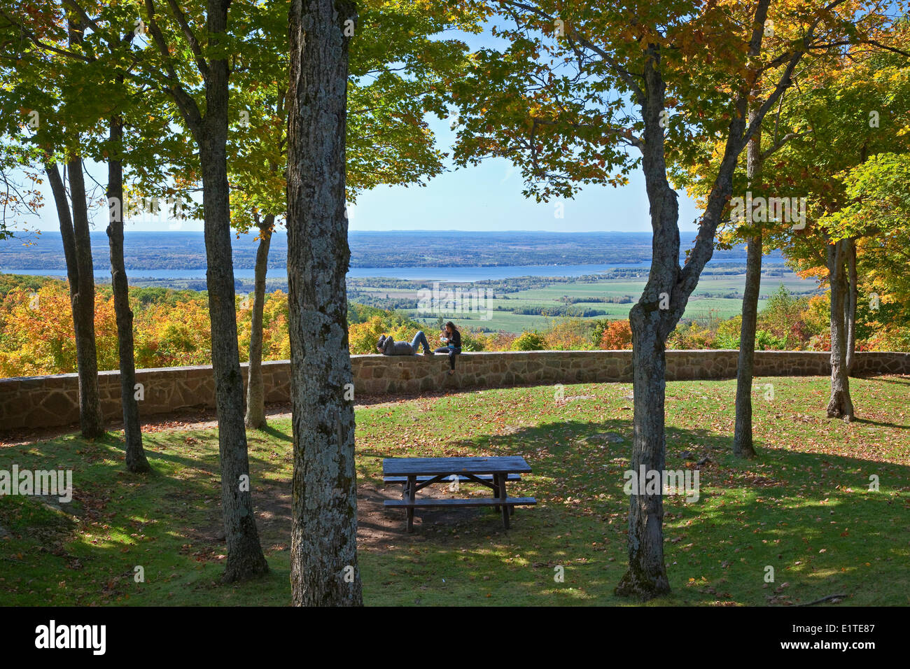 Couple sitting on stone masonry guardrail overlooking the Ottawa River, Gatineau Park, Gatineau, Quebec, Canada. - Stock Image