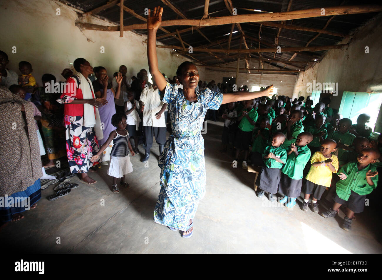 Villagers and school children dance at a NGO funded school in the Nyagatare district of Rwanda - Stock Image