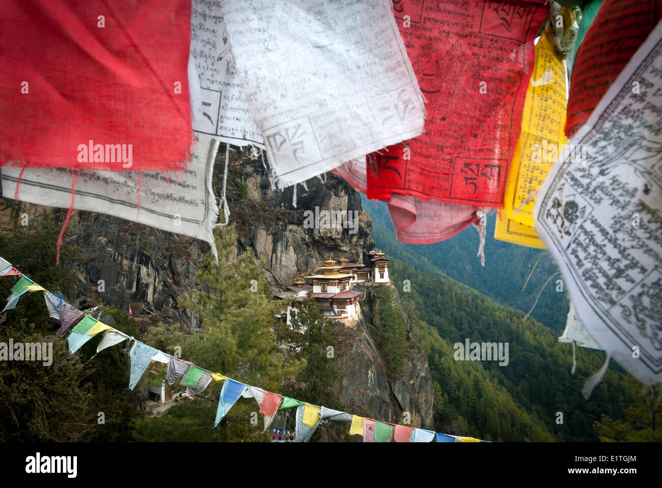 Taktsang (Tigers Nest) Monastery peeks out behind some prayer flags above Paro, Bhutan - Stock Image