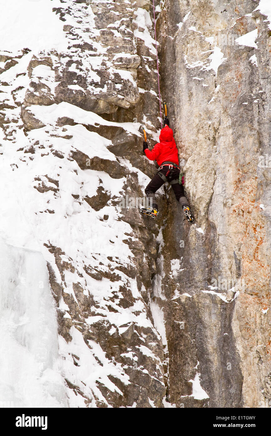 Young man climbs a mix of ice and rock while ice-climbing in Banff National Park near Banff, Alberta, Canada. - Stock Image
