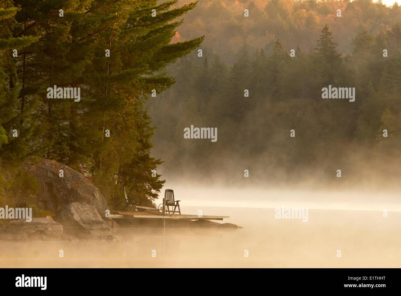 Dock and Muskoka Chair on Smoke Lake, Algonquin Park, Ontario - Stock Image