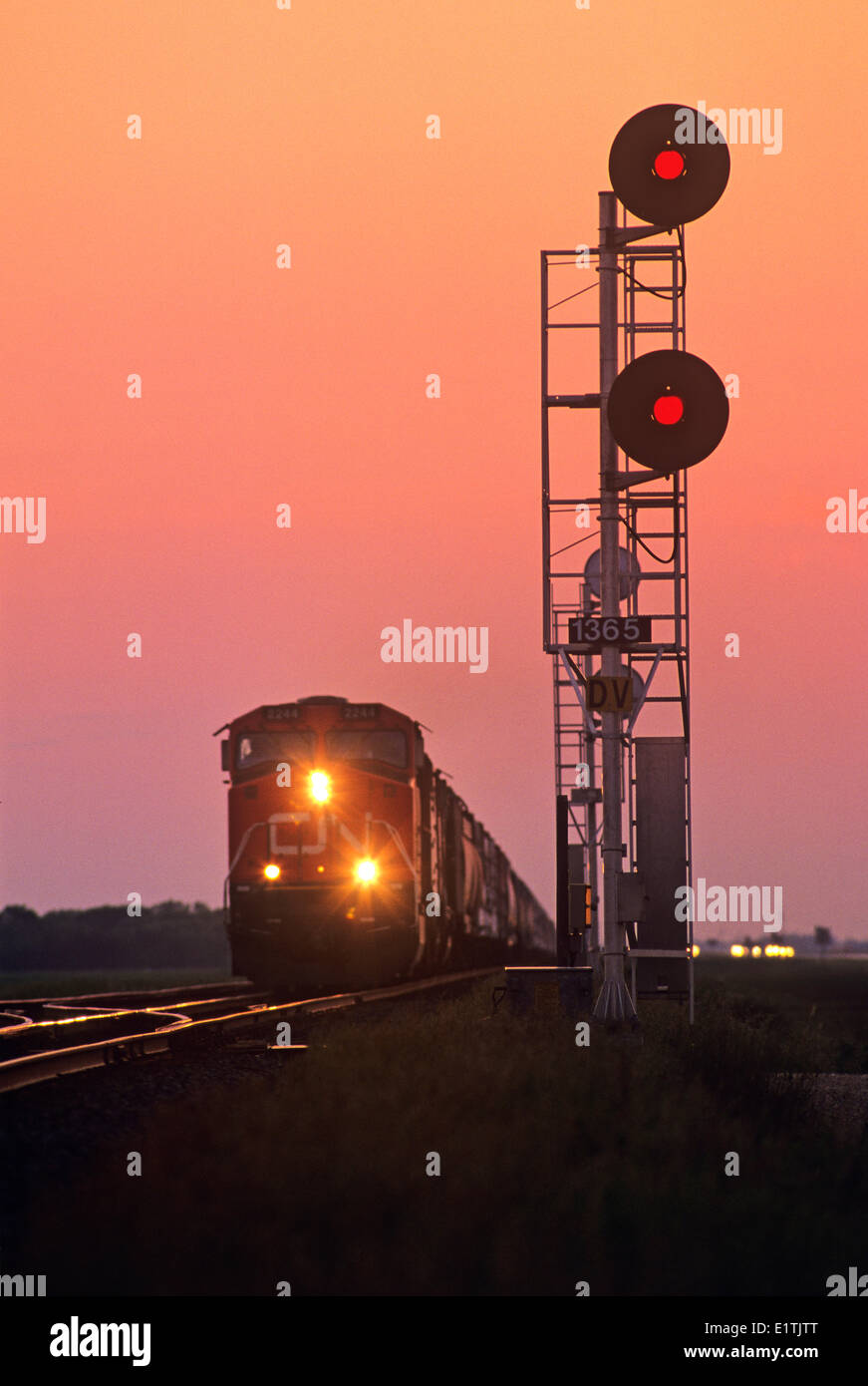 close up of rail signal with approaching train in the background, near Winnipeg, Manitoba, Canada - Stock Image