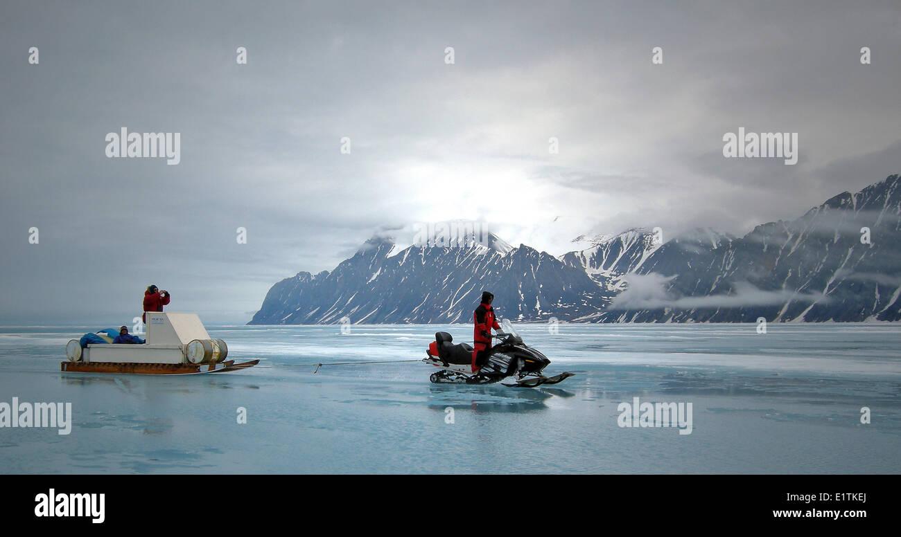 Ski-doo towing Inuit Kkomatik, Pond Inlet, Nunavut - Stock Image
