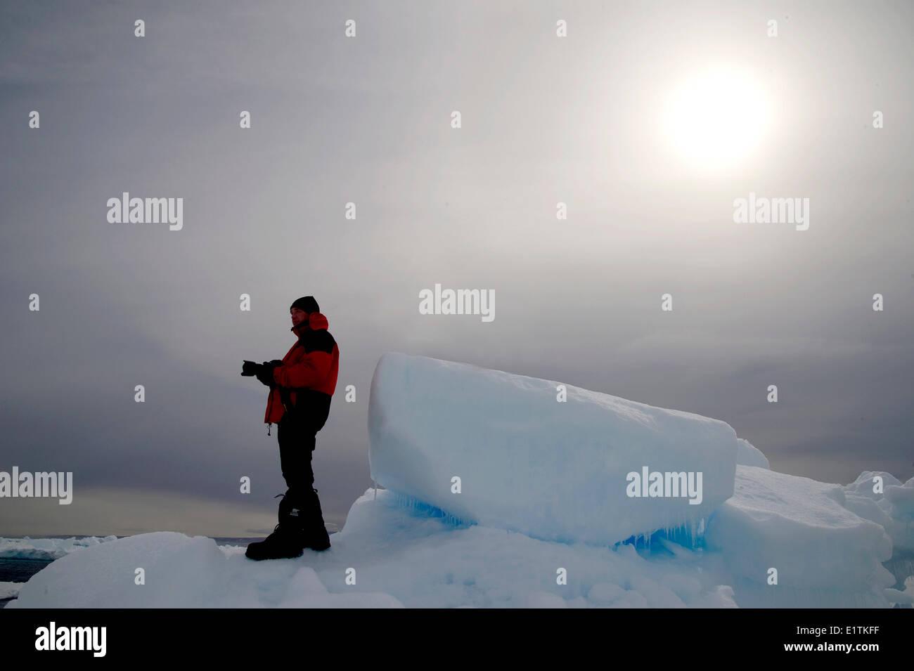 Photographer on floe-edge, Arctic Bay, Nunavut, Canada - Stock Image
