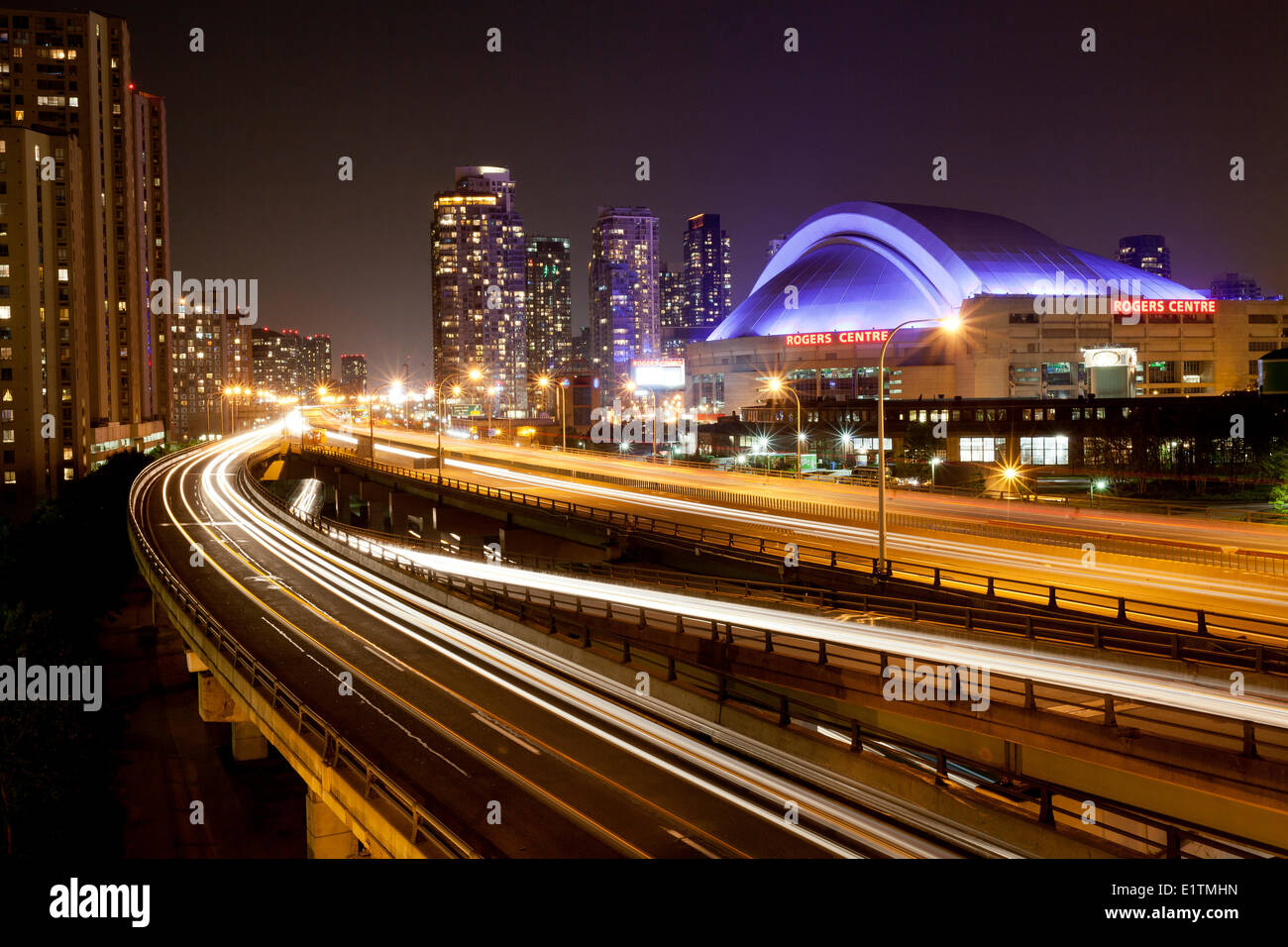 Evening view the Gardiner Expressway the Rogers Centre (formerly called the Skydome) lit with purple lights in downtown Toronto - Stock Image