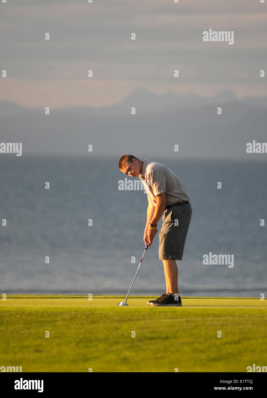 A young golfer lines up his final putt,  Qualicum Beach, Central Vancouver Island, British Columbia, Canada - Stock Image