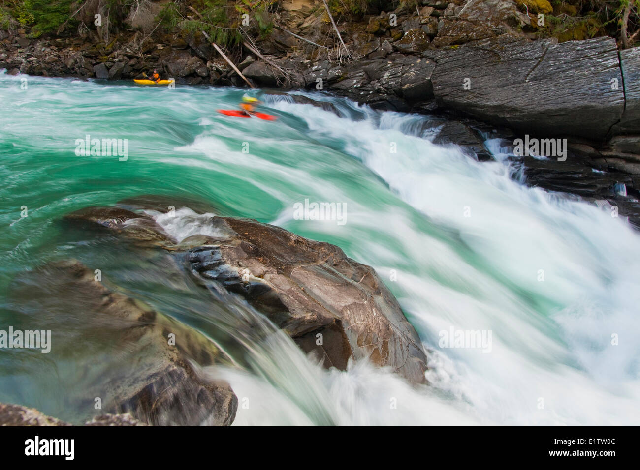 Two male kayakers drop into a big rapid on the Fraser River, Mt Robson Provincial Park, BC - Stock Image