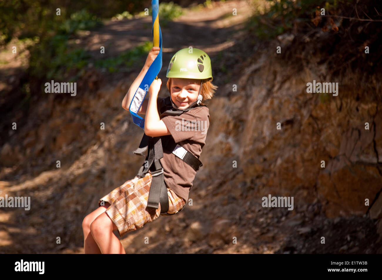 Young boy enjoys zip-line at Oyama Zipline, Okanagan Valley, BC, Canada. - Stock Image