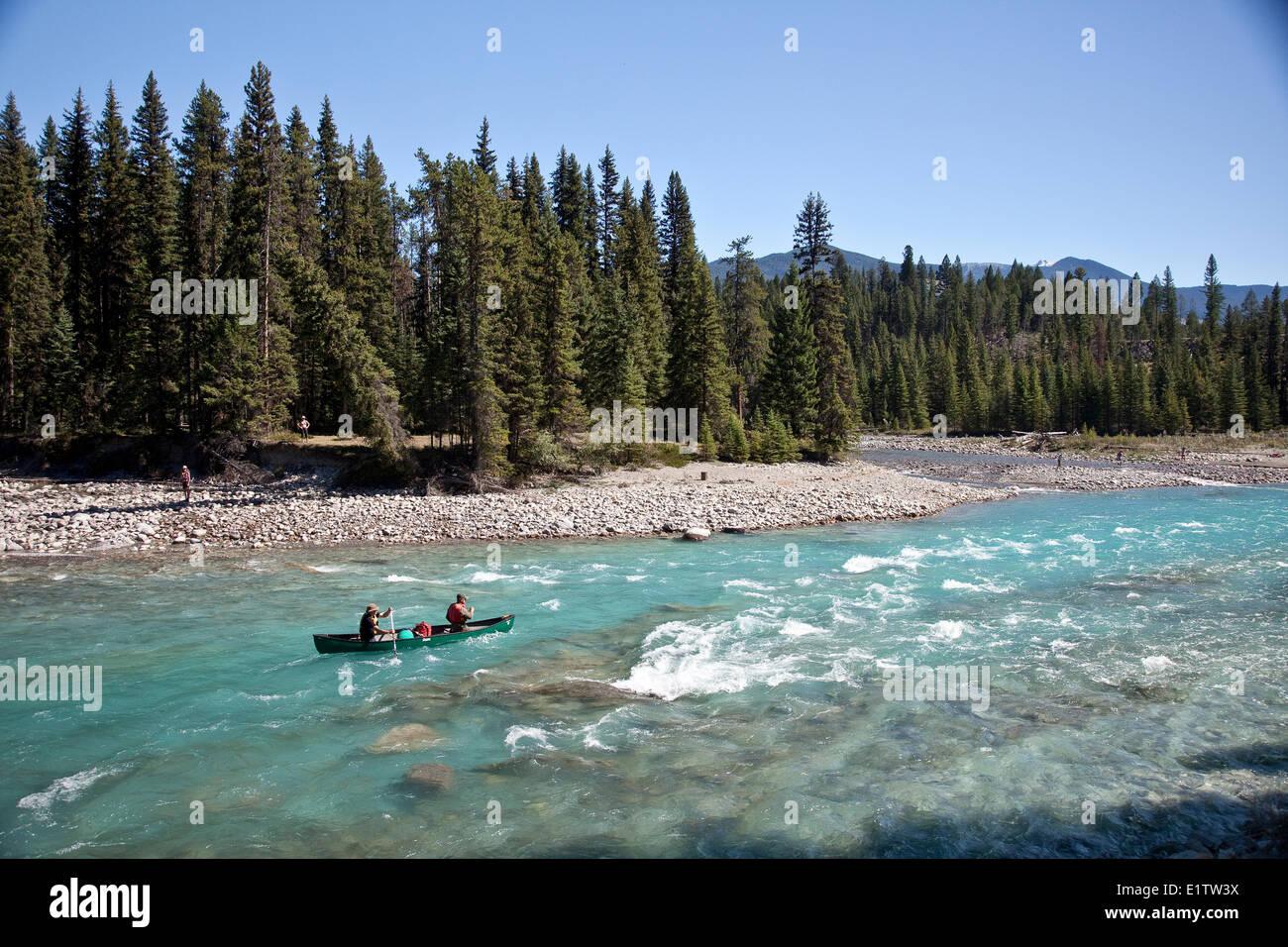 Two men paddle canoe on Kootenay River, Kootenay National Park, BC, Canada. - Stock Image