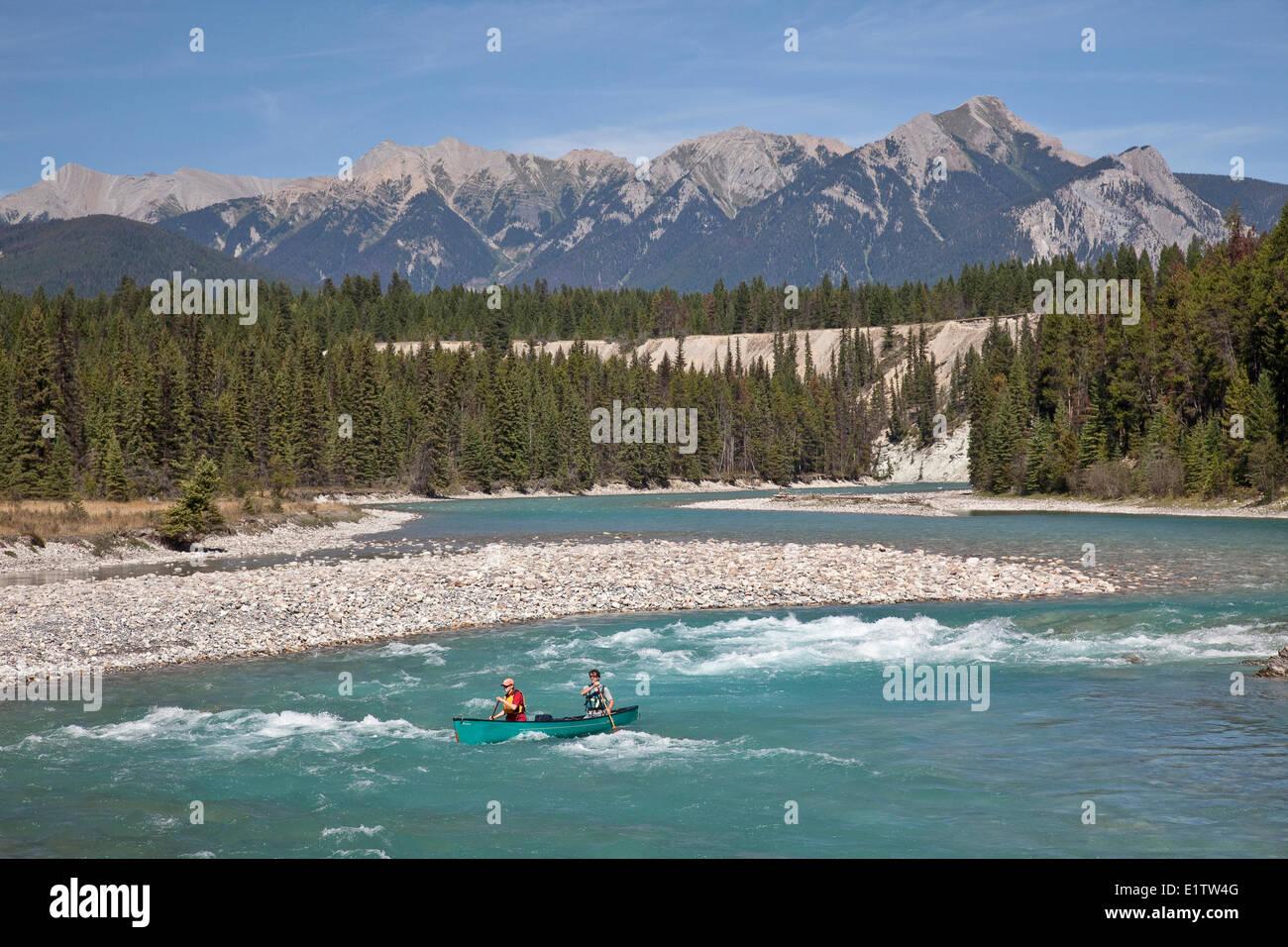 Couple paddle canoe through rapids on Kootenay River, Kootenay National Park, BC, Canada. - Stock Image