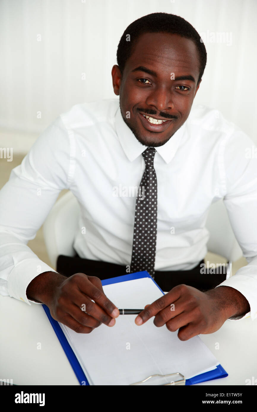 African man sitting at the table and signing document in office - Stock Image