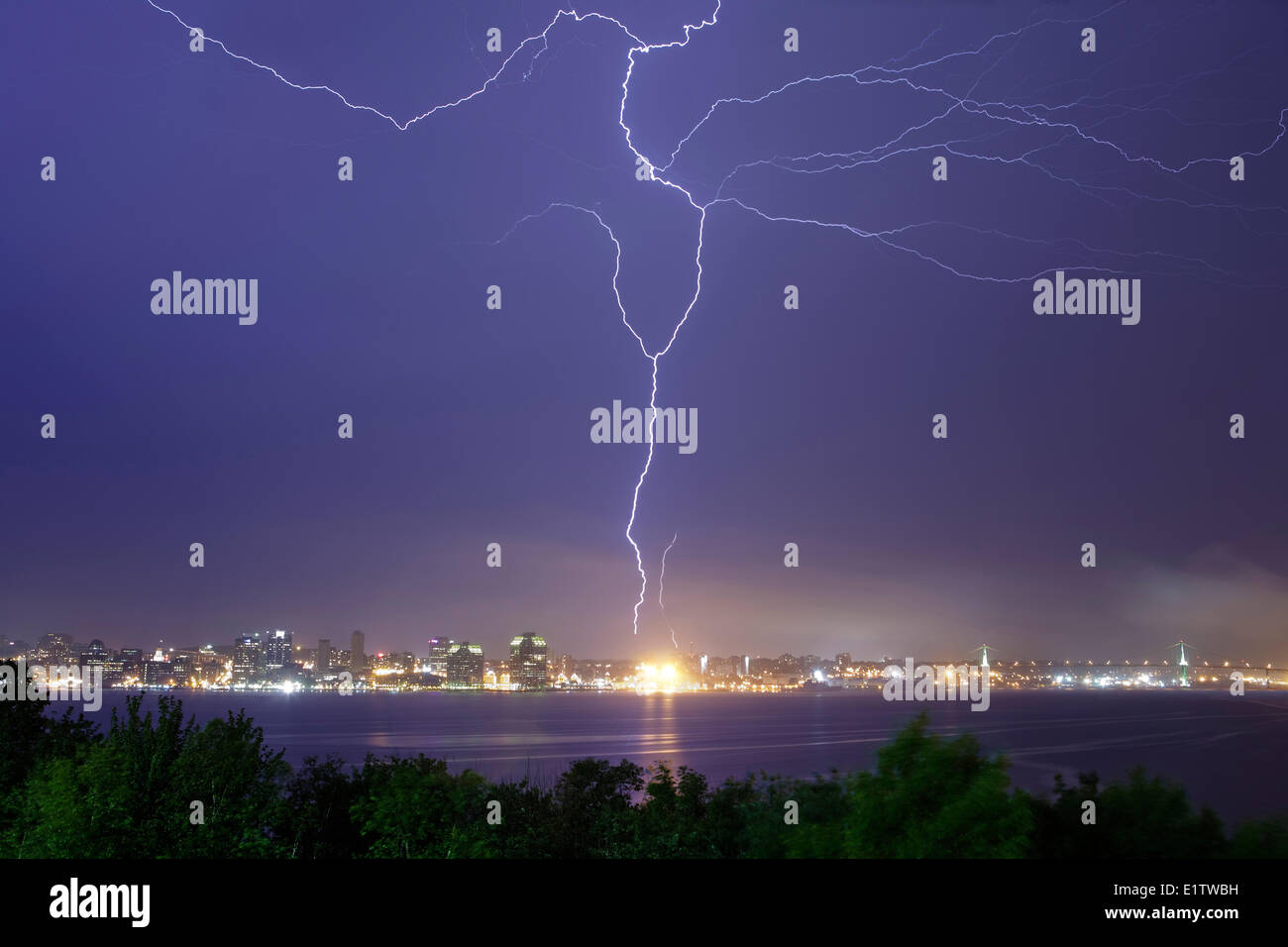 A bolt lightning fills the sky over Halifax Harbour and strikes a communications tower in Halifax, Nova Scotia - Stock Image