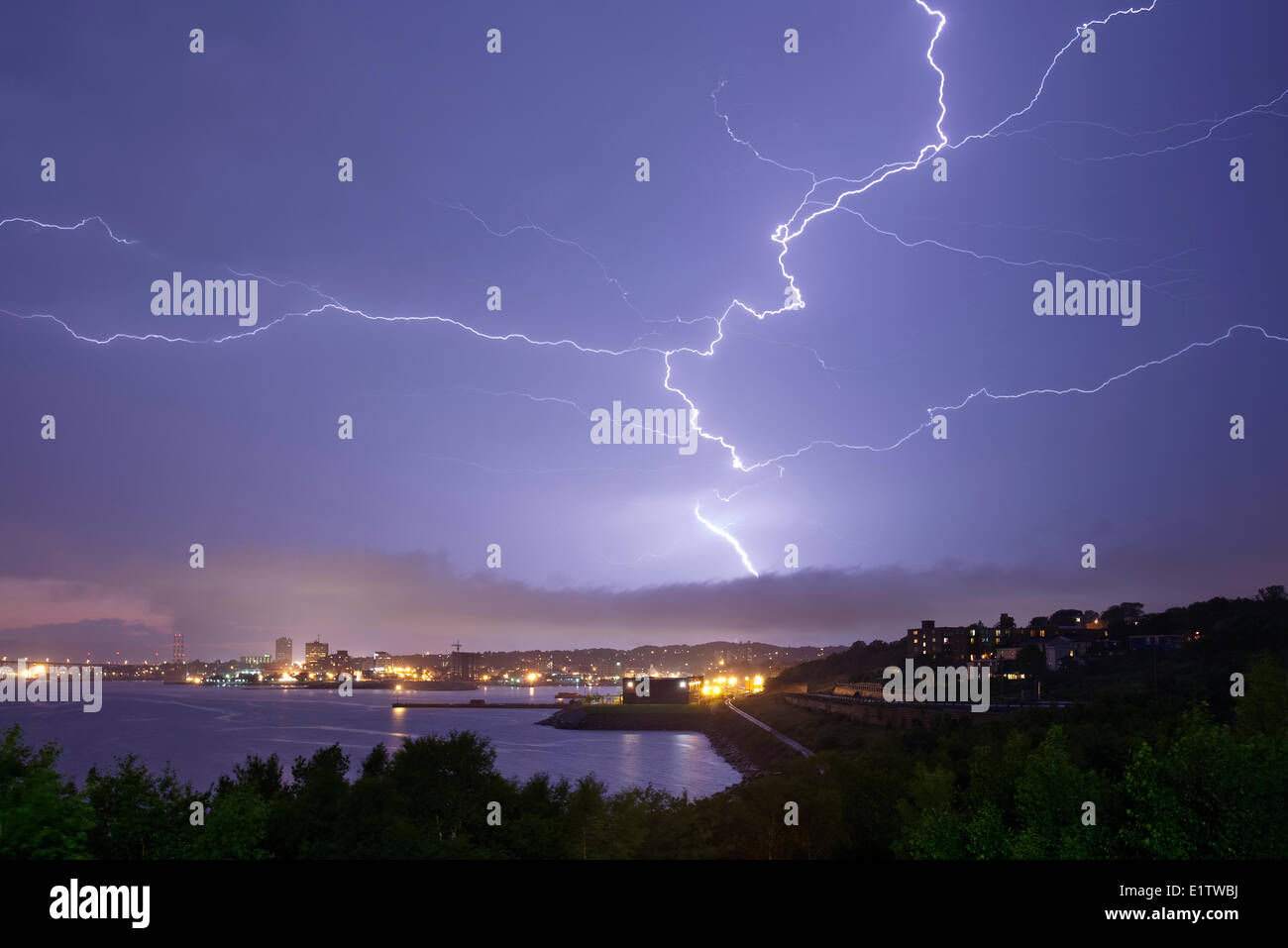 A bolt of cloud to cloud lightning fills the sky over Halifax Harbour and Dartmouth, Nova Scotia - Stock Image