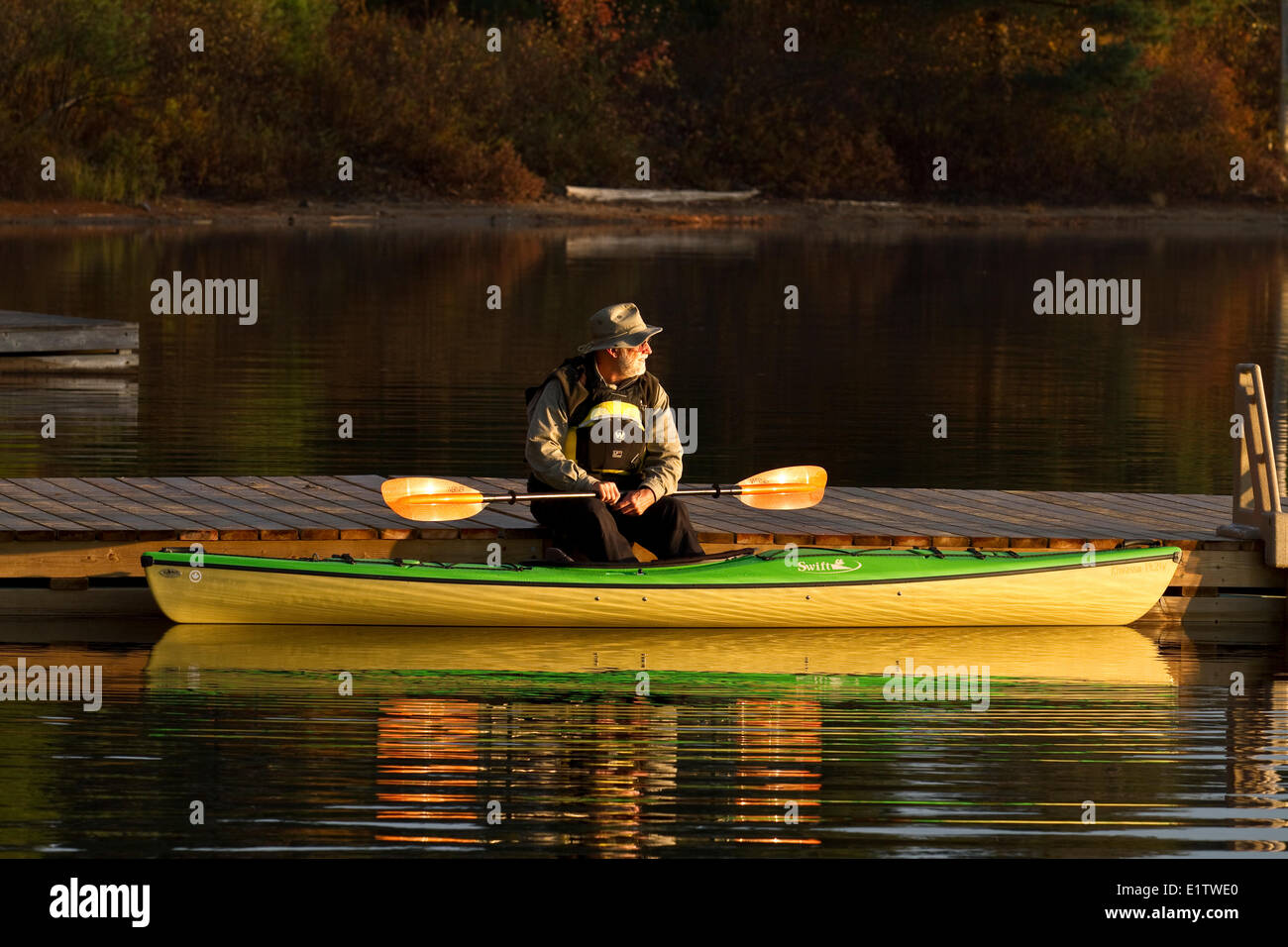 Elderly man enjoys quiet morning on dock with kayak on Oxtongue Lake, Muskoka, Ontario, Canada. - Stock Image